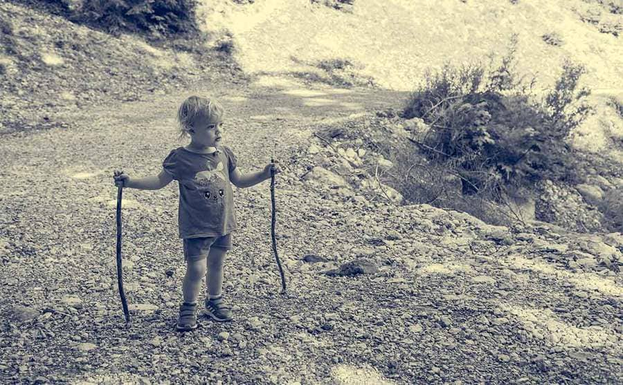 Cute blonde girl standing on a mountain path holding a pair of walking sticks