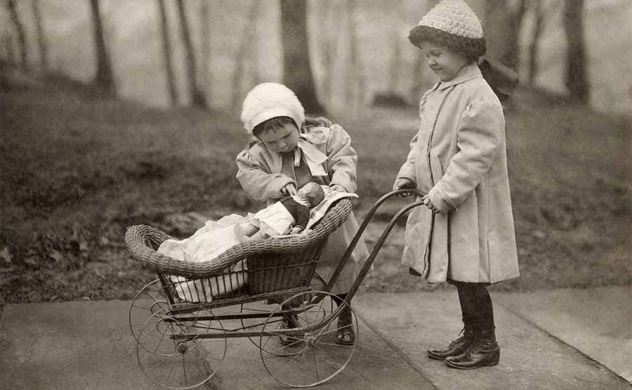 Two young girls playing with a Campbell Kid doll and a baby carriage in a park