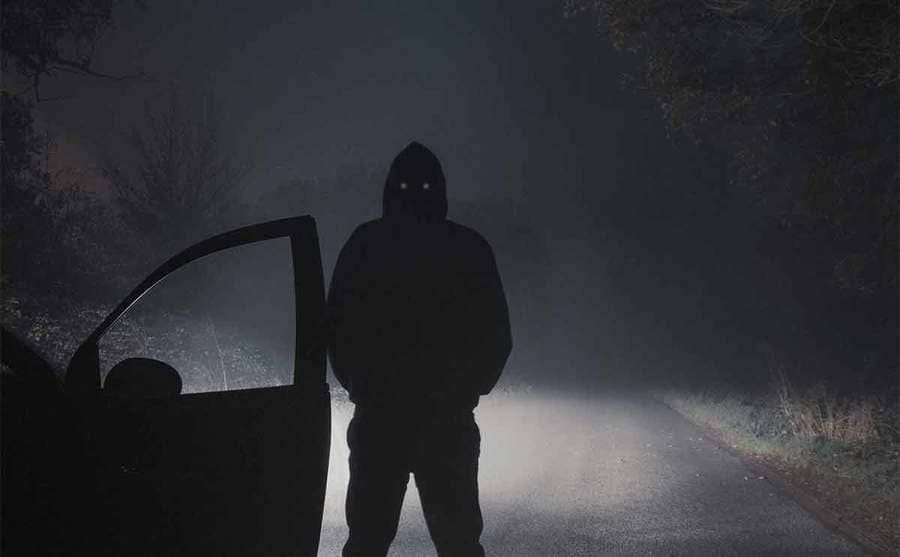 A man standing next to a car with the door open parked at the side of the road on a foggy night