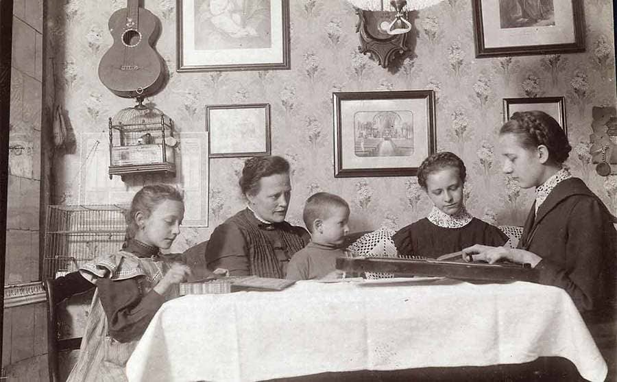 A mother and her children at the dinner table circa the 1910s