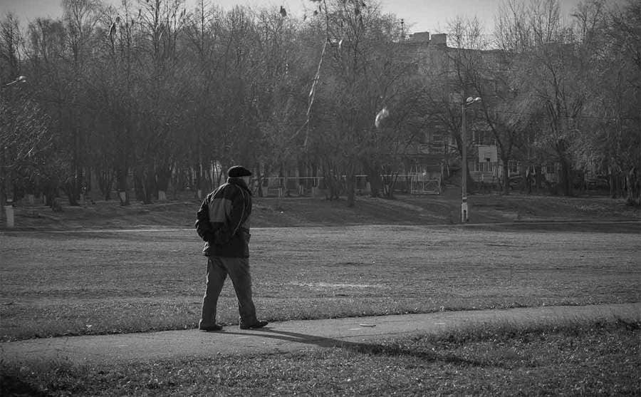 An older man walking alone in the park