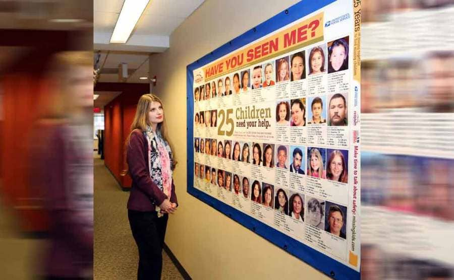 A woman standing next to a bulletin board with missing children on it