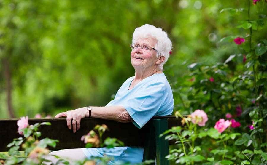 A woman smiling sitting on a park bench