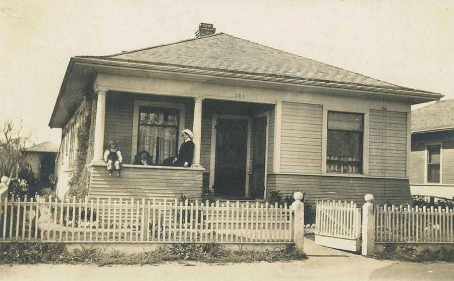 A family sitting outside of their house circa the 1900s