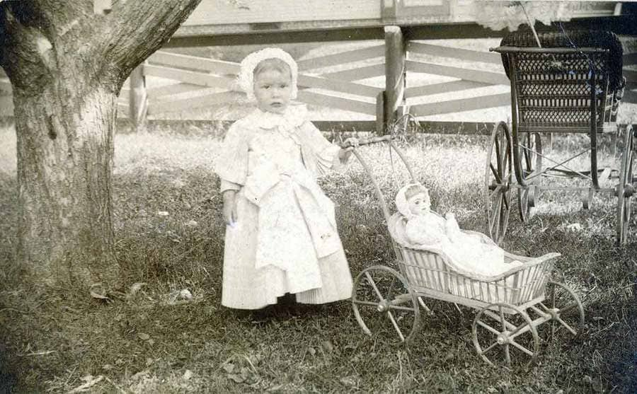 A young child with a doll carriage photographed in the early 1900s