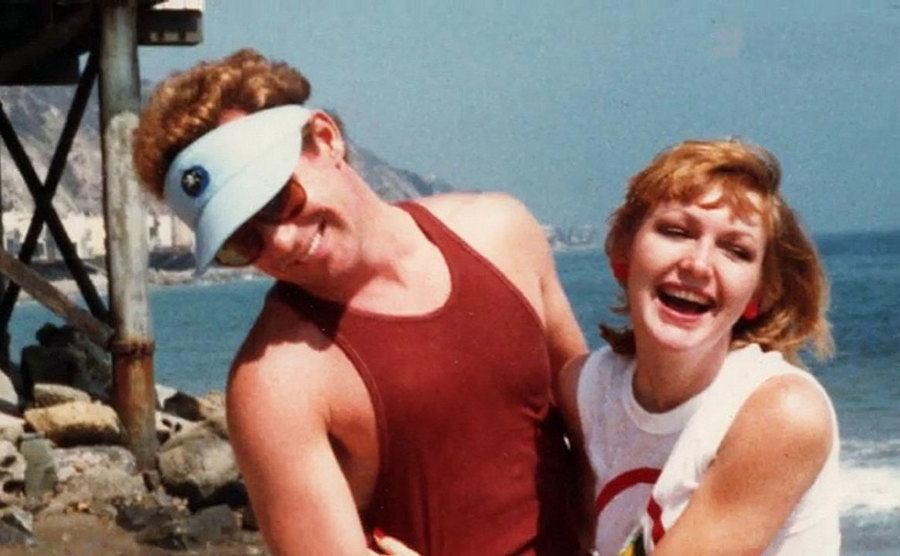 Phil Hartman and Lisa Jarvis posing together at the beach