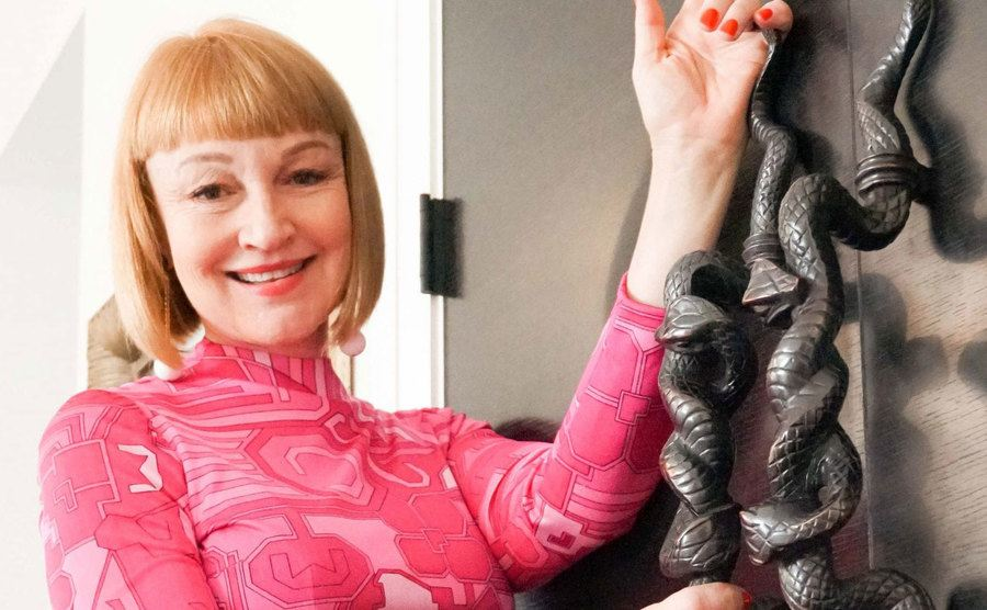 Lisa Jarvis posing next to a closet with handles in the shape of snakes