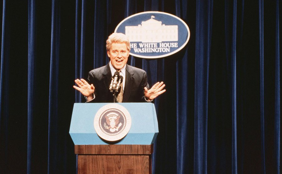 Phil Hartman standing behind a podium with the presidential seal in a skit from SNL