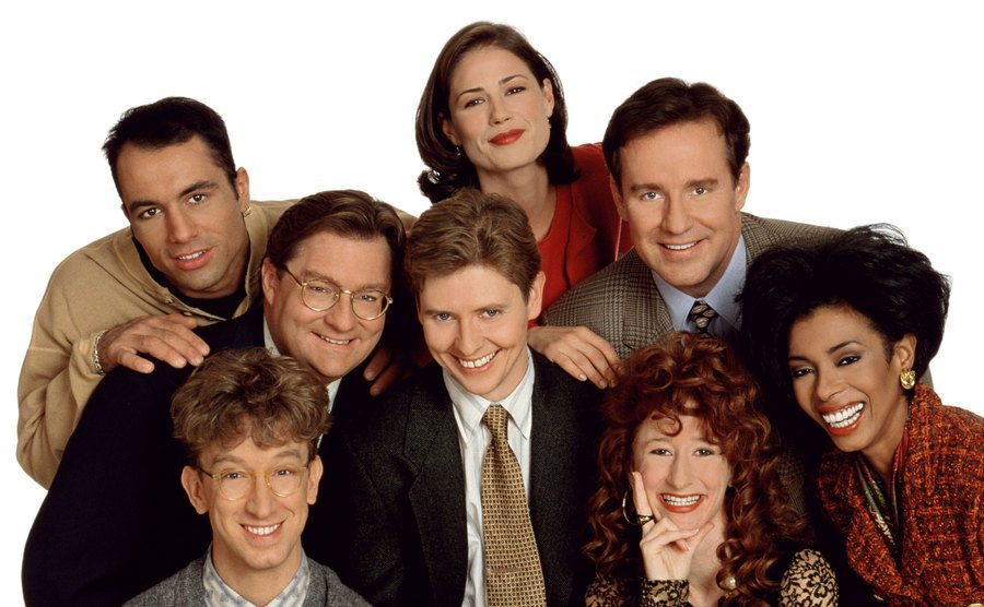 Maura Tierney, Joe Rogan, Phil Hartman, Stephen Root, Dave Foley, Vicki Lewis, Khandi Alexander, and Andy Dick posing together in a promotional shot of the cast of Newsradio