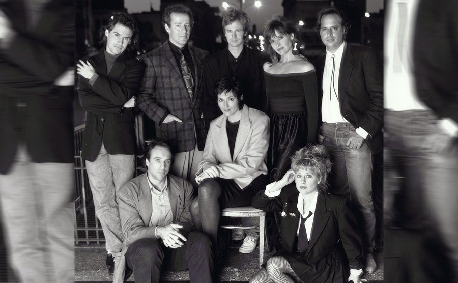 Dennis Miller, Phil Hartman, Dana Carvey, Jan Hooks, Jon Lovitz, Kevin Nealon, Nora Dunn, and Victoria Jackson posing together on steps as the cast of Saturday Night Live