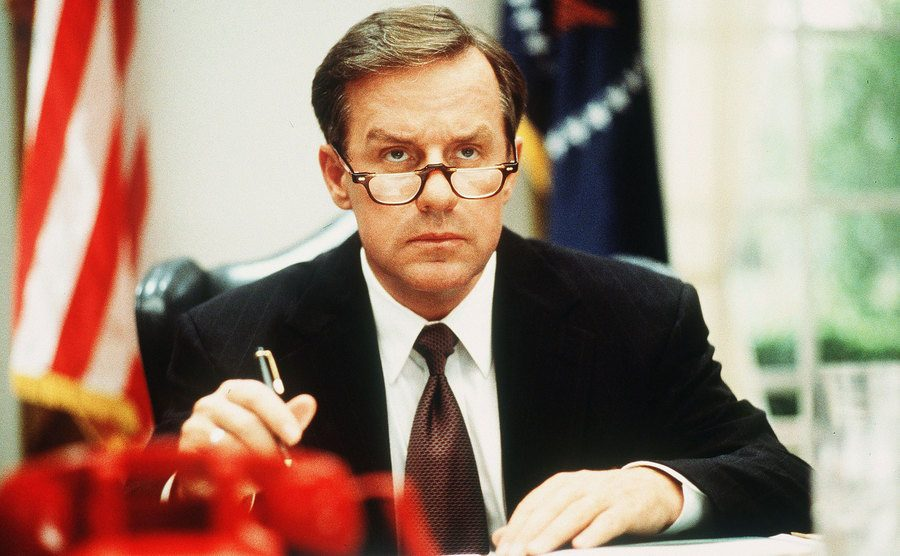Phil Hartman in The Second Civil War sitting behind a desk with a red telephone in front of him