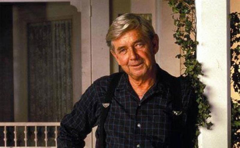 Ralph Waite standing on a porch