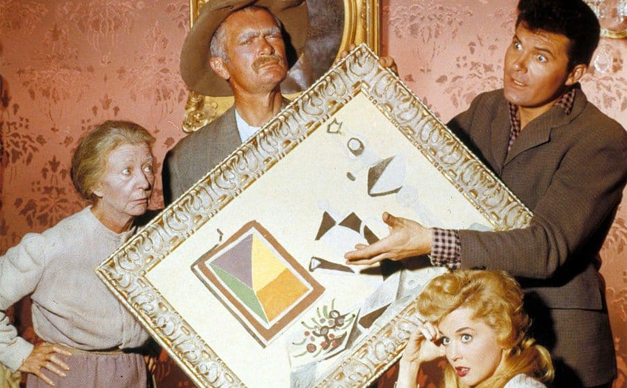 Irene Ryan standing next to Buddy Ebsen and Max Baer holding a picture, Donna Douglas sitting beneath them