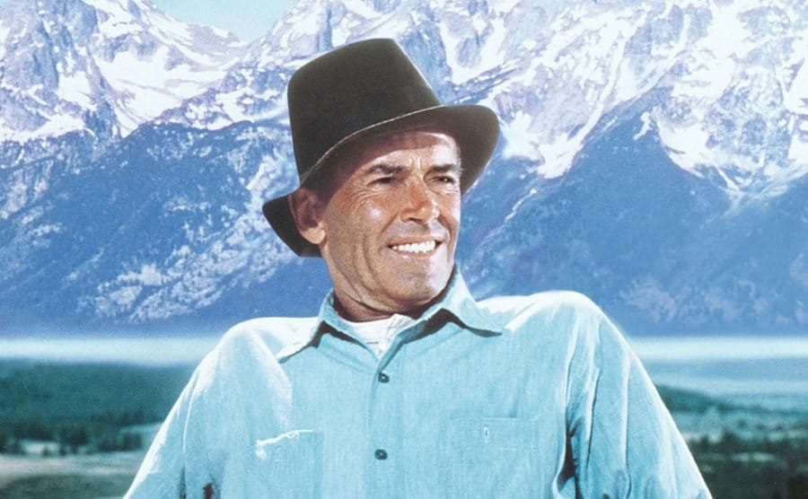 Henry Fonda standing in front of snowy mountains looking ahead