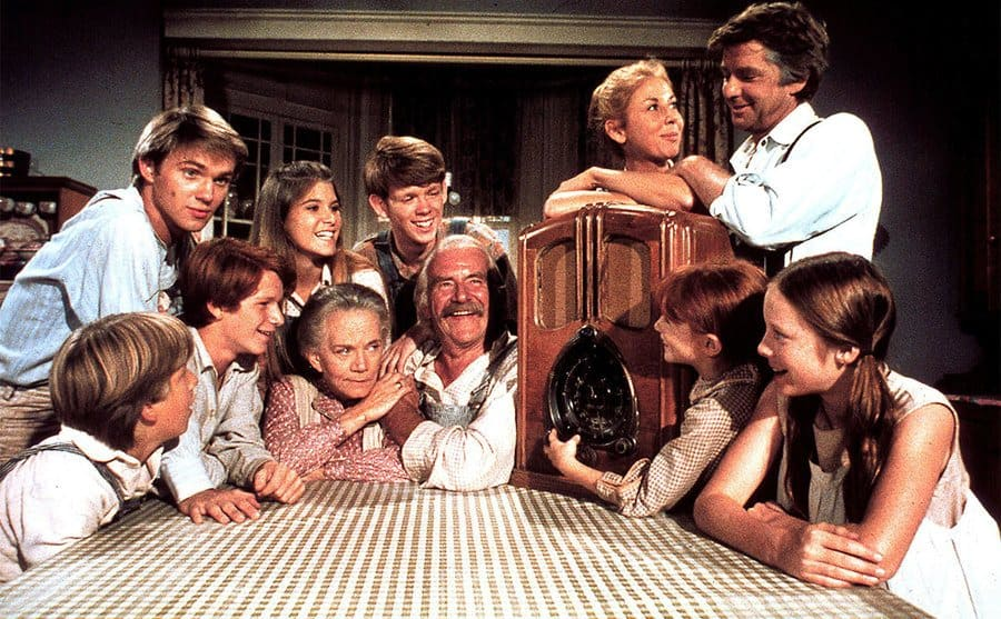 The Waltons sitting together around a table