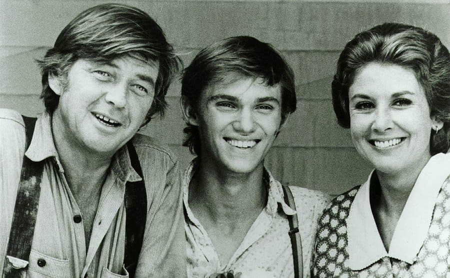 Ralph Waite, Richard Thomas, and Michael Learned standing at a porch