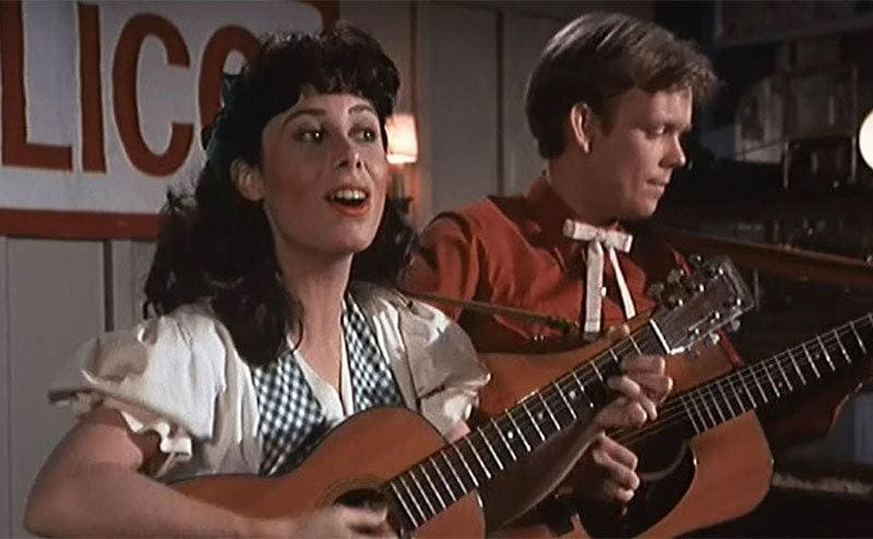 Lisa Harrison and Jon Walmsley playing a guitar and singing together