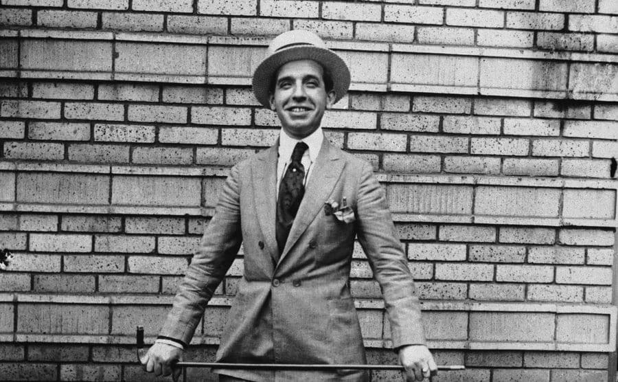 Charles Ponzi posing holding a cane in front of a brick building