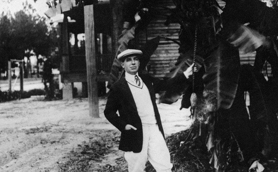 Charles Ponzi standing in front of a palm tree