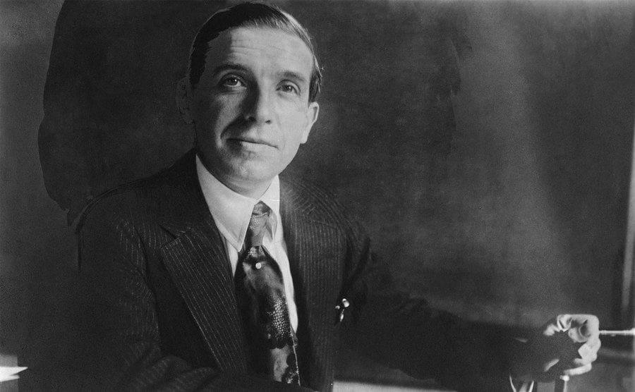 Charles Ponzi sitting behind his bank desk