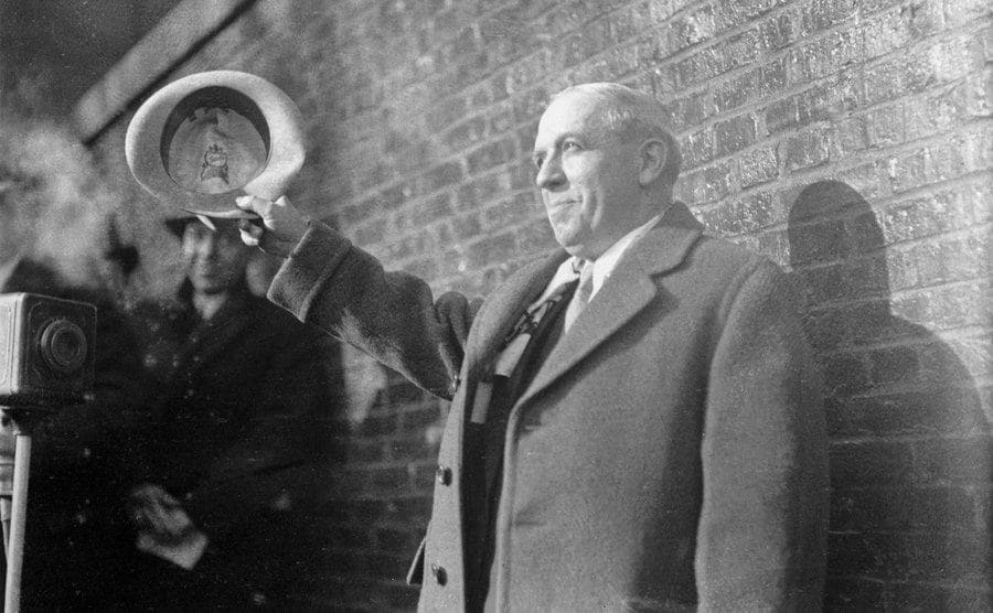 Charles Ponzi waving his hat in front of cameras standing in front of a brick wall