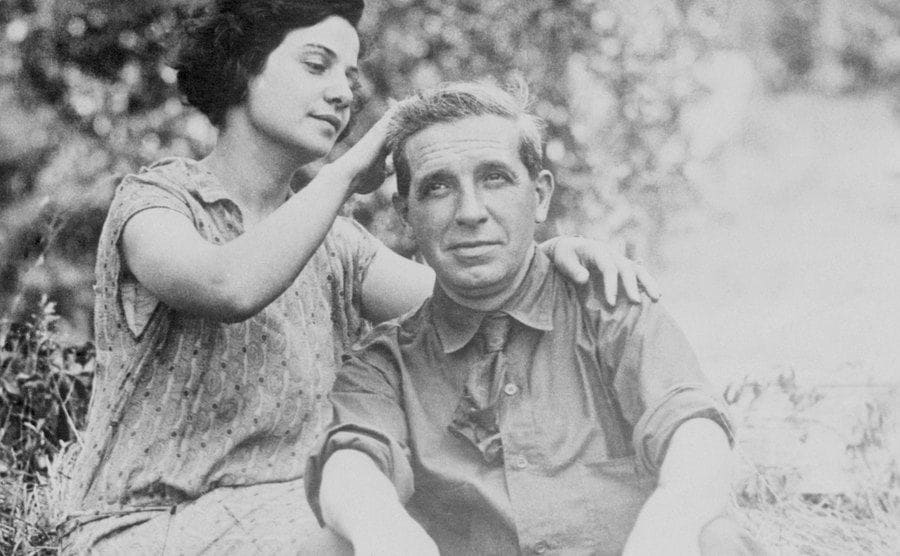 Rose Ponzi stroking Charles hair sitting in a field together