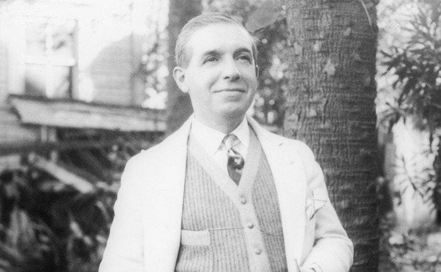 Ponzi standing in a yard in front of a tree trunk wearing a tailored suit