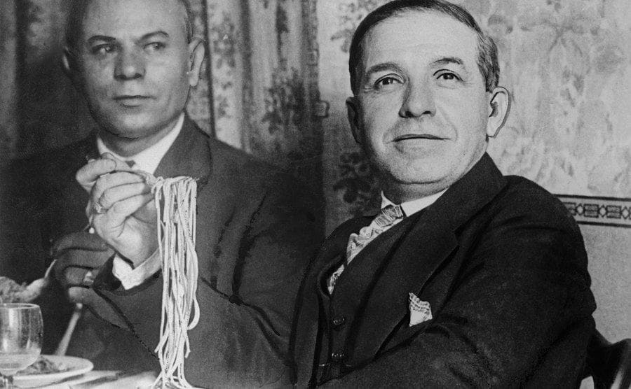 Charles Ponzi eating spaghetti at a dinner dable with a man to his right
