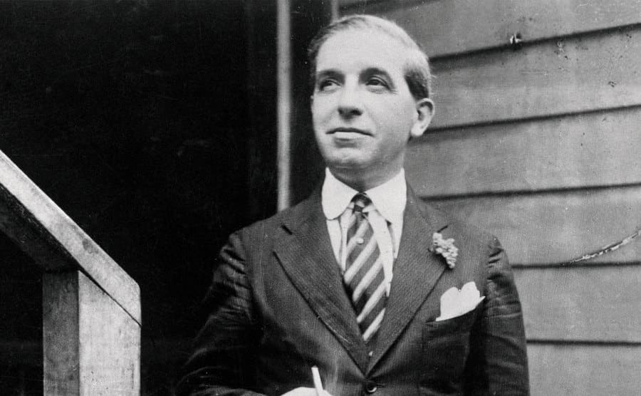 Charles Ponzi standing on a staircase