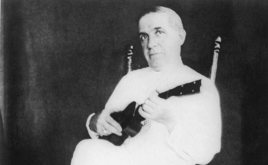 Charles Fonzi playing a ukeleili sitting in a wicker chair
