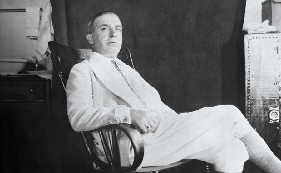Charles Ponzi wearing an all white suit relaxing in a chair