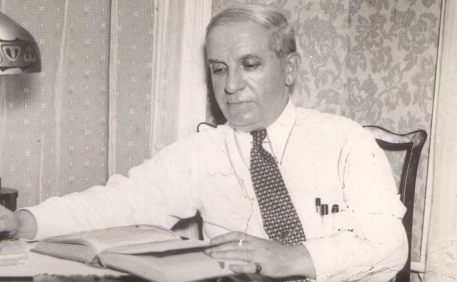 Charles Ponzi sitting at a desk reading a book