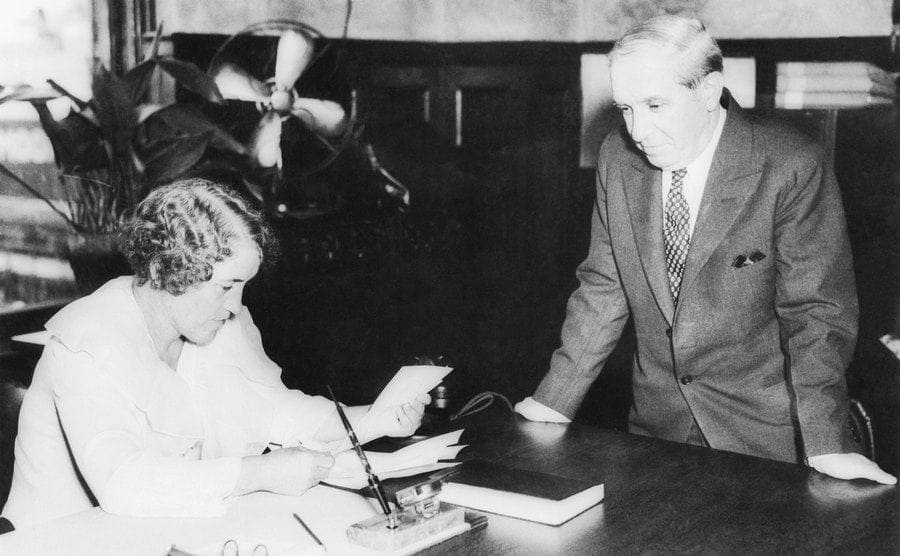 Charles Ponzi standing next to a woman who is sitting behind a large fancy desk