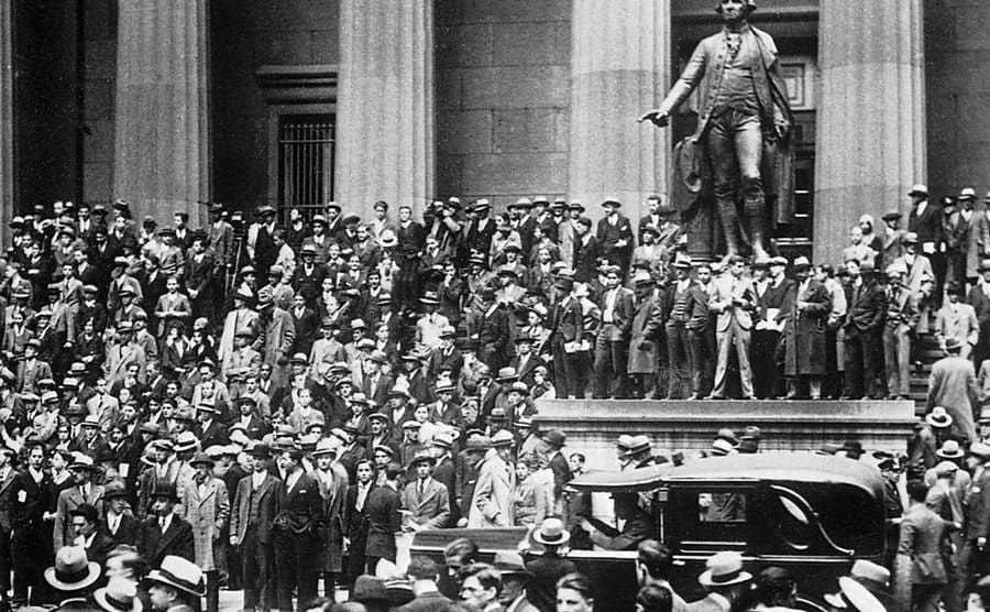 After the news of the Wall Street crash, a crowd of speculators, worried about the fall of their financial securities, have gathered in front of the New York Stock Exchange near where a statue of George WASHINGTON stands.