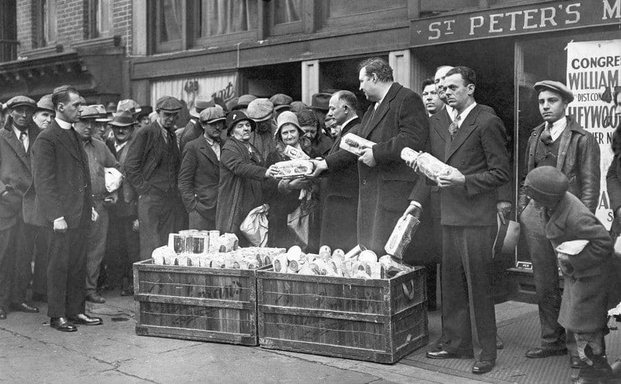 William I. Sirovich, Heywood Brown, and Reverend Raymond Brown hand out packages of food to the jobless outside St. Peter's Mission in New York City.