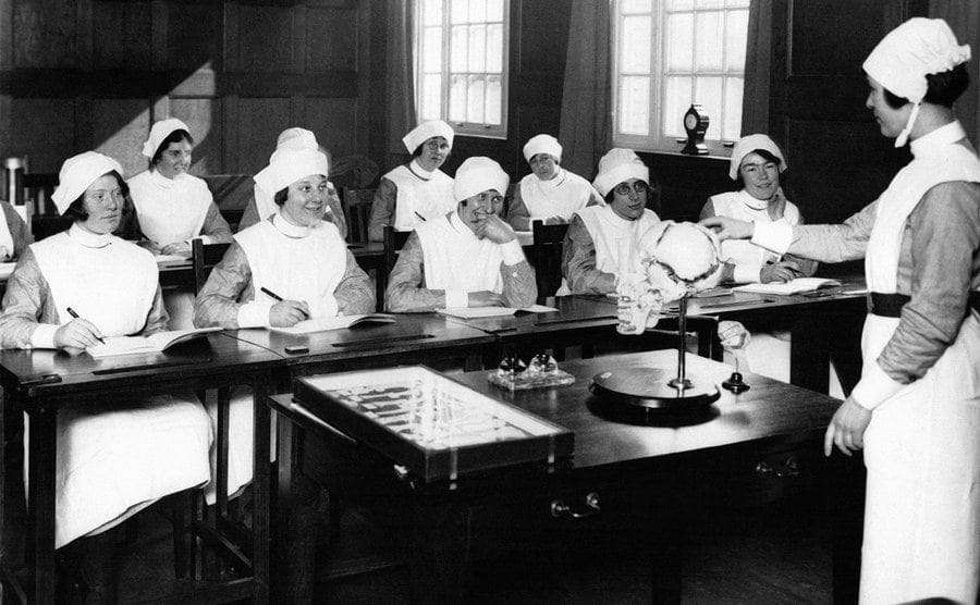 Women Dressed as nurses in class learning about the human skull.
