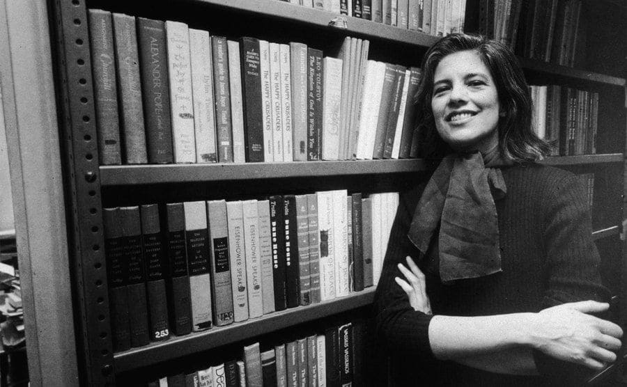Portrait of American author and critic Susan Sontag, she smiles broadly as she leans, arms crossed, against a bookshelf.