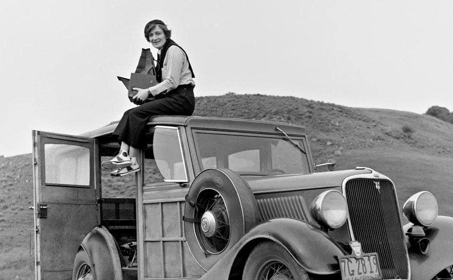 Dorothea Lange sitting on top of a car with her camera, ca. 1936.