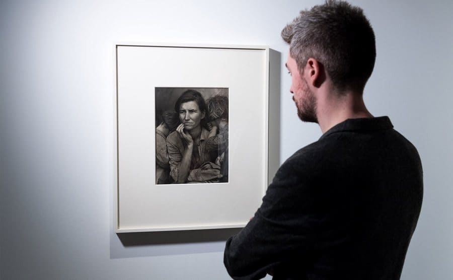 A visitor looks at the 'Migrant Mother' photograph hanging in a museum.