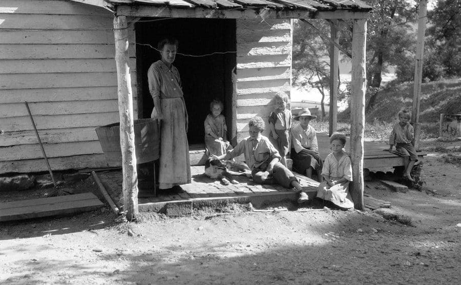 Farm woman with six children on the porch of clapboard farmhouse, 1930.
