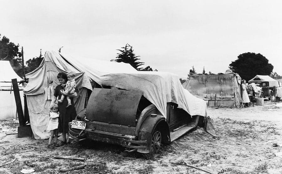 A broken down car of a family looking for work in the pea fields during the Great Depression.