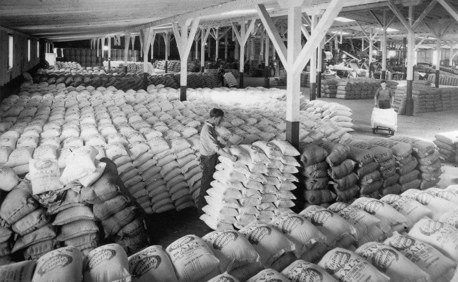 Men moving bags around in a general stock room filled with food supplies.