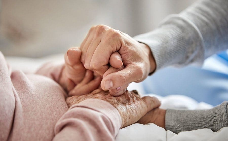 A care nurse holding the hand of an elderly woman.