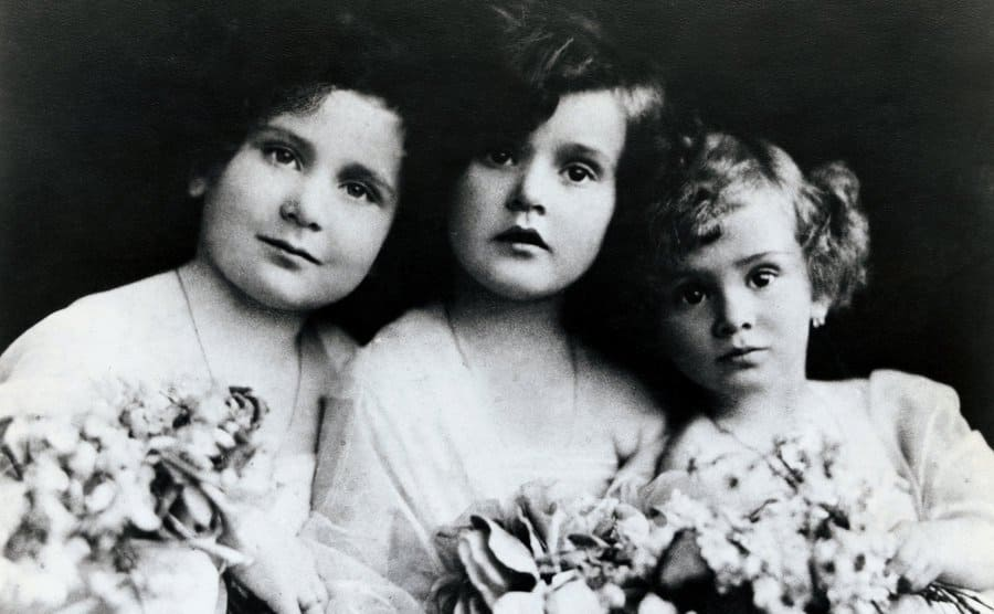 The Gabor sisters posing holding flowers