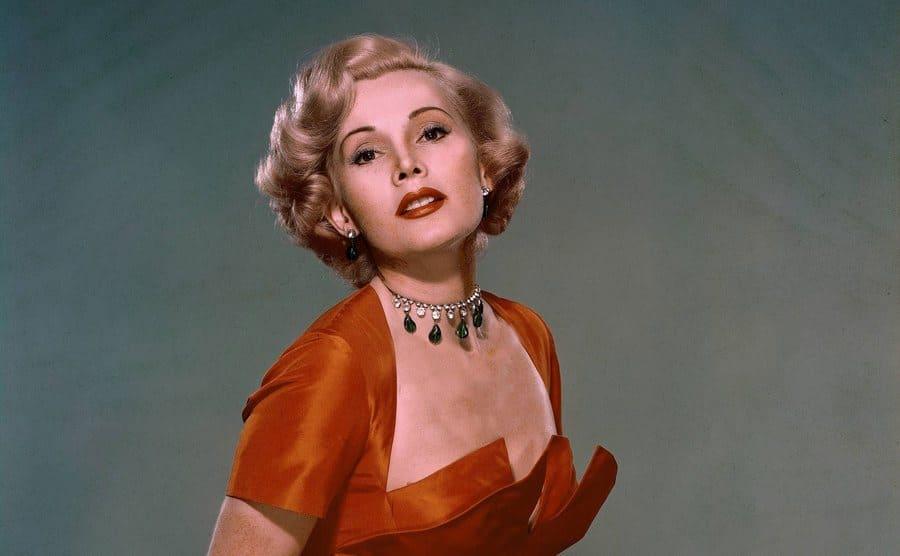Zsa Zsa Gabor wearing an orange dress posing for a portrait