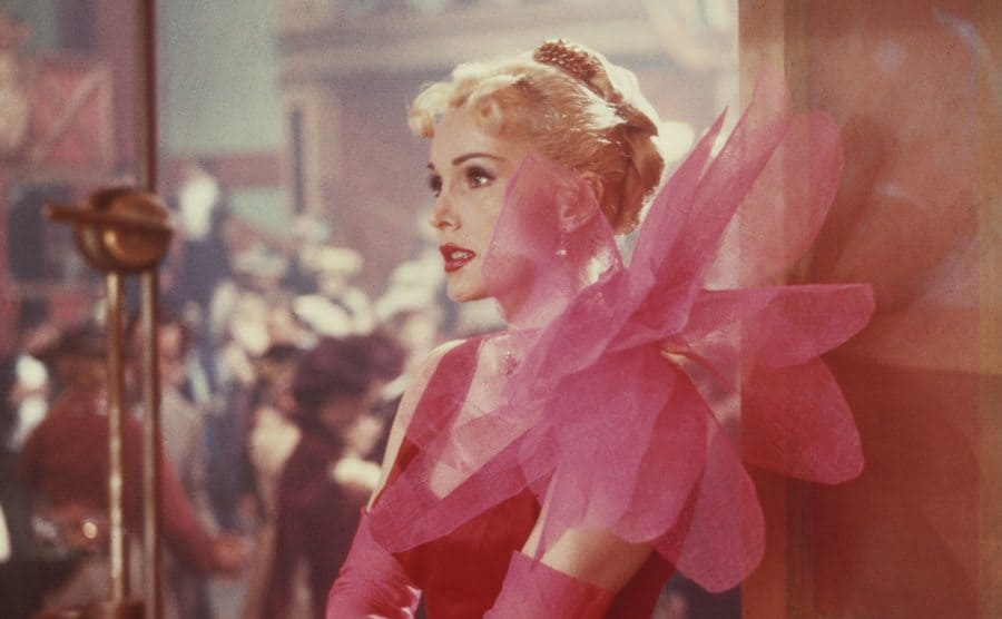 Zsa Zsa Gabor wearing a pink dress with a large accent piece sticking off of her shoulder while leaning against a wall