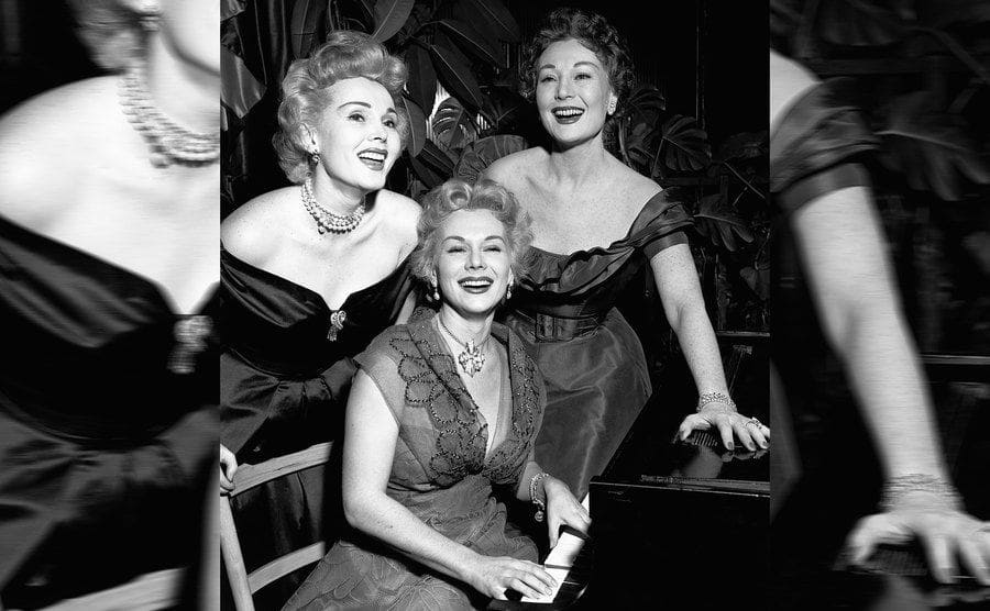 The Gabor sisters laughing around the piano while Eva plays
