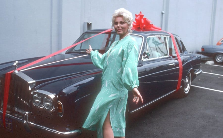 Zsa Zsa Gabor pointing to her new Rolls Royce with a large red ribbon on it