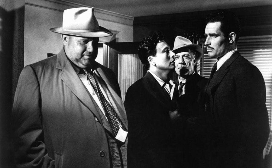 A man confronting a group of men in a room in a scene from the film Touch of Evil
