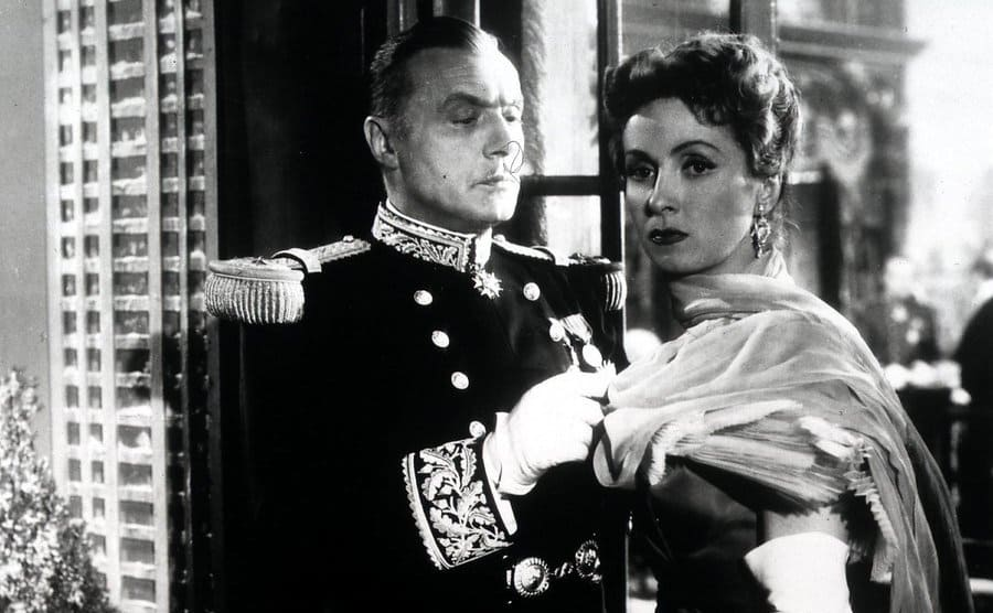 Danielle Darrieux standing next to Charles Boyer standing in front of a window dressed up in a scene from a film